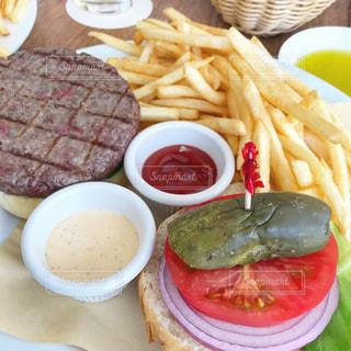 ハンバーガー、フライド ポテト、テーブルの上に食べ物のプレートの写真・画像素材[1106106]