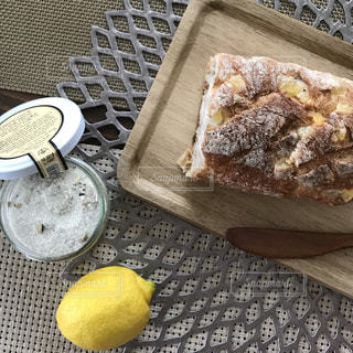 テーブルの上のパンと木製のまな板とレモンと塩の写真・画像素材[1106127]