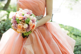 花を持っているドレス姿の女性の写真・画像素材[1106172]