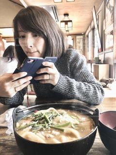 食事の写真を撮るのに夢中になっている女性の写真・画像素材[1107543]