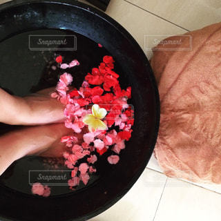 両足を花を浮かべた水の入った容器に入れている人の写真・画像素材[1107575]