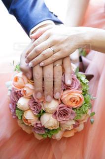 ピンクのブーケの上に重ねた男女の手の写真・画像素材[1108263]