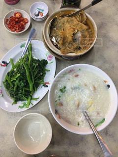 テーブルの上の皿の上に食べ物のボウルの写真・画像素材[1330225]