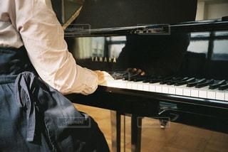 ピアノの前に立っている男の写真・画像素材[1881796]