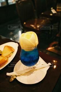 テーブルの上に青と白の皿が置いてあるグラスの写真・画像素材[2311510]