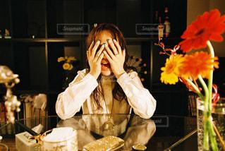 テーブルの上の花瓶の隣に立っている人の写真・画像素材[2381502]