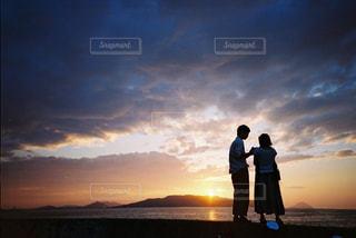 夕焼けの前に立っている男女の写真・画像素材[2381528]
