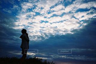 曇り空の前に立っている男の写真・画像素材[2381540]