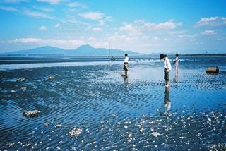 水域の隣に立つ人々のグループの写真・画像素材[2381546]