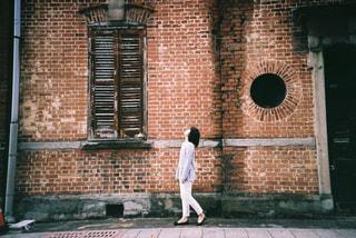 レンガ造りの建物の前に立っている人の写真・画像素材[2381552]
