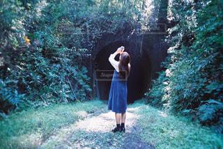 トンネルの前でスマホをかかげる少女の写真・画像素材[2381589]