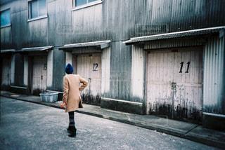 建物の隣の通りを歩いている男の写真・画像素材[2381603]