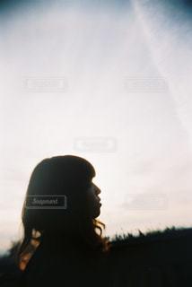 夕焼けの前に立っている人の写真・画像素材[2381608]