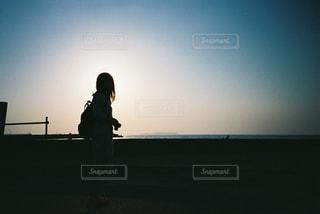 夕焼けの前に立っている人の写真・画像素材[2381619]