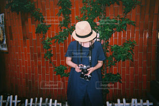レンガの壁の前に立っている人の写真・画像素材[2381662]
