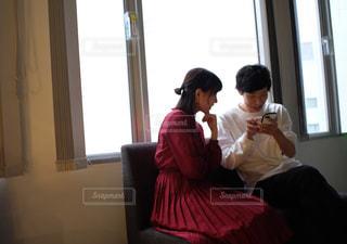 窓の前に座っている男女の写真・画像素材[2691457]