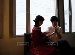 窓の前に座っている男女の写真・画像素材[2691458]