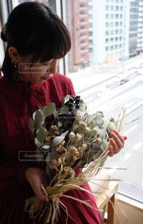 花瓶のあるテーブルに座っている人の写真・画像素材[2698786]