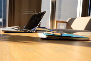 木製のテーブルの上に座っているラップトップコンピュータ付きの机の写真・画像素材[2934652]