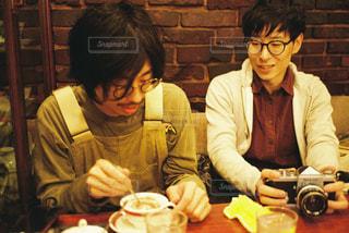 レストランのテーブルに座っている人々のグループの写真・画像素材[2939094]