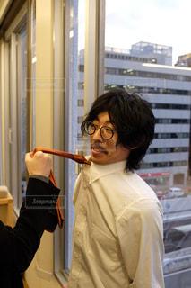 カメラに向かってポーズをとる鏡の前に立っている人の写真・画像素材[2943898]