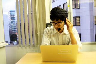 在宅でオンライン会議中のスーツ男性の写真・画像素材[2943937]