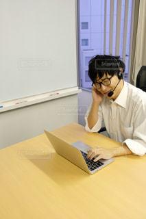 ラップトップを使ってテーブルに座っている人の写真・画像素材[2943940]