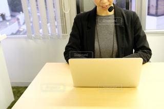ノートパソコンを持ってテーブルに座って、カメラに向かって微笑む男性の写真・画像素材[2945204]