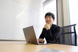 窓の前の机に座っている人の写真・画像素材[2949683]