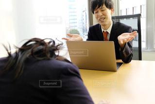 ラップトップの前のテーブルに座っている人の写真・画像素材[2949701]