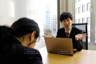 ラップトップの前のテーブルに座っている人の写真・画像素材[2949700]