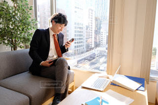 ラップトップを使ってテーブルに座っている男の写真・画像素材[2949746]
