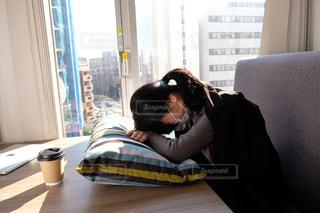 窓の前のテーブルに座っている人の写真・画像素材[2949748]