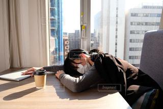 窓の前のテーブルに座っている人の写真・画像素材[2949750]