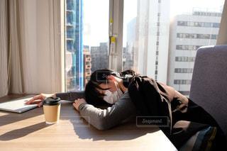 窓の前のテーブルに座っている人の写真・画像素材[2949753]