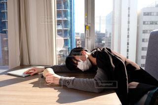 窓の隣に座っている人の写真・画像素材[2949755]