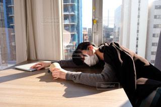 窓の前に座っている人の写真・画像素材[2949758]