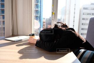 窓の前の机に座っている人の写真・画像素材[2949760]