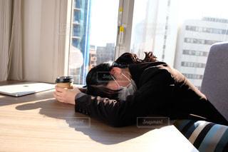 窓の隣で寝ている人の写真・画像素材[2949762]