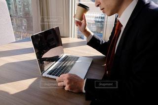 ラップトップコンピュータを使ってテーブルに座っている男性の写真・画像素材[2949773]