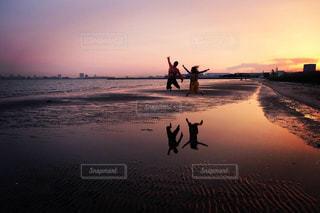 水域の近くのビーチで馬に乗っている男の写真・画像素材[2961921]
