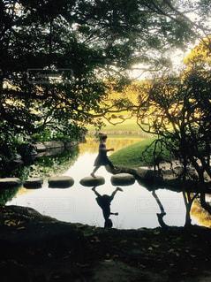 池を渡る少女の写真・画像素材[1130563]