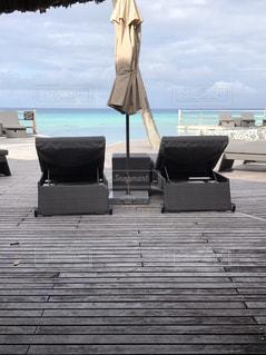 ビーチの前に座っている椅子の写真・画像素材[1125700]