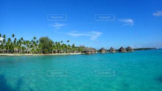 水の体の横に座っている青と白のボートの写真・画像素材[1125708]