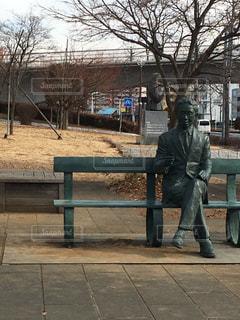 公園のベンチに座っている銅像の写真・画像素材[1125253]