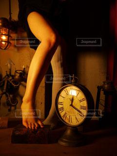 時計の前に立っている女性足の写真・画像素材[1131003]