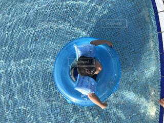 浮き輪でプールに浮く男の子の写真・画像素材[1127372]