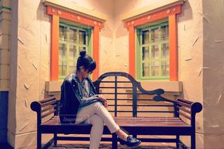 建物の前にあるベンチに座っている女性の写真・画像素材[1127346]