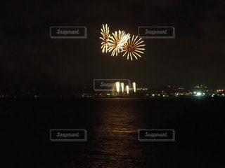 水の体の上の夜空に花火の写真・画像素材[1128804]