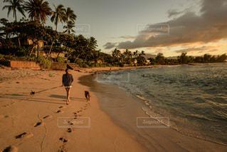 水の体の近くのビーチの上を歩く人々 のグループの写真・画像素材[1129614]